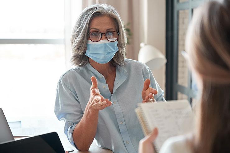 Une personne portant un masque, en pleine entrevue.