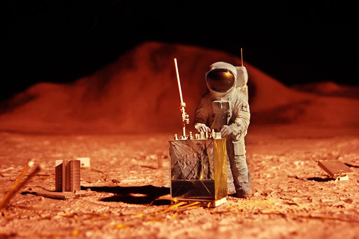Figurines d'astronautes en bois dans un paysage montagneux