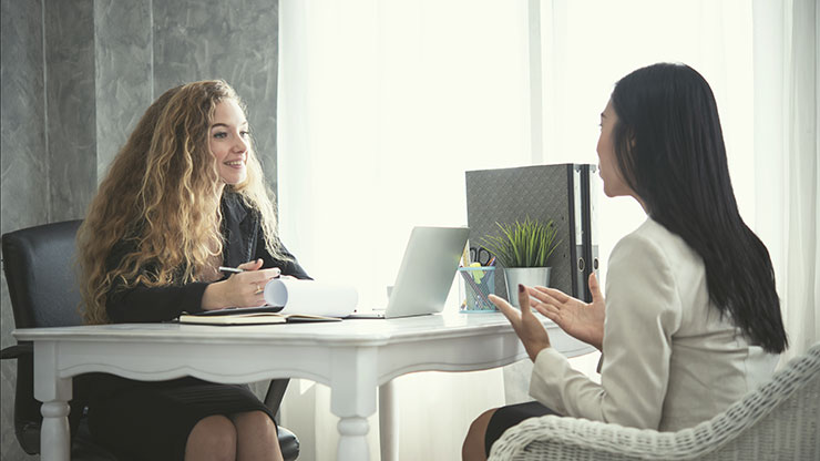 Pros and cons of using a staffing agency: Woman interviewing with human resources professional