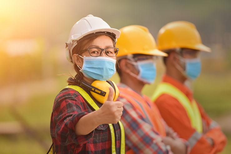 Une femme portant un EPI, le pouce en l'air, dans un entrepôt