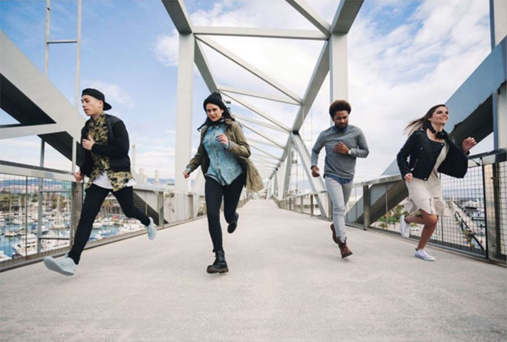 Un groupe de jeunes heureux courent en avant.