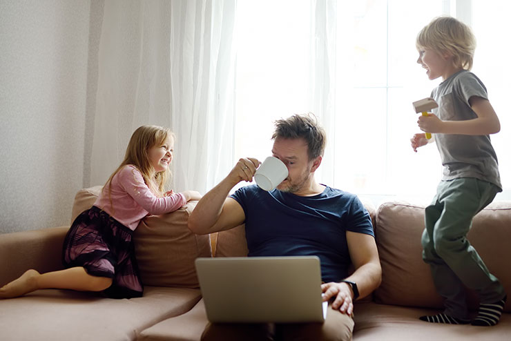 Man working while sitting on sofa with children playing beside him