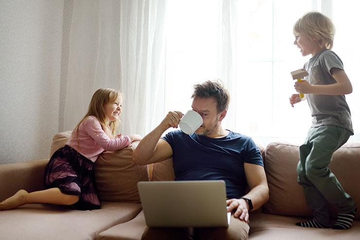Homme travaillant assis sur un canapé, des enfants jouant près de lui