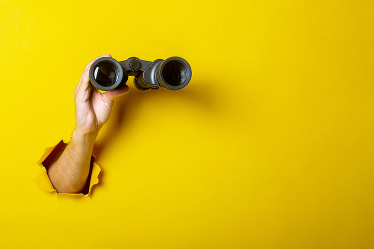 Arm holding binoculars against yellow wall