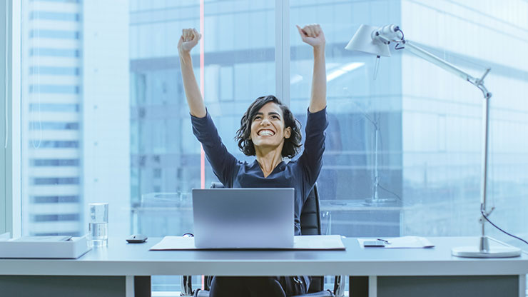 Person at desk with arms raised in triumph