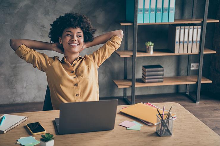 Personne qui sourit, assise à son bureau