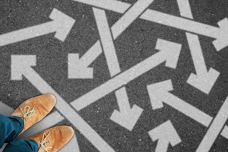 Image of pavement with multiple arrows pointing in different directions with person's legs and shoes in lower left-hand corner.