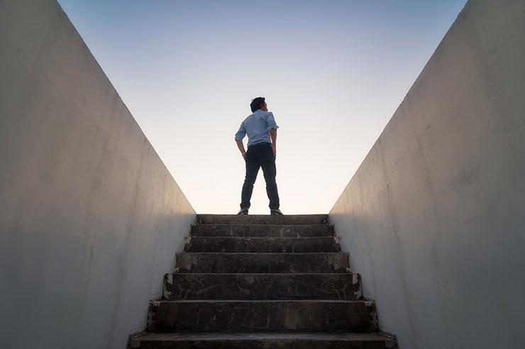 Une personne se tient en haut d'un escalier souterrain, en regardant le ciel