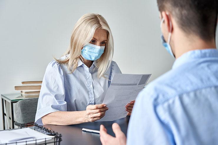 Entretien entre deux personnes portant des masques.