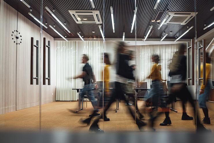Image floue de gens qui marchent dans un espace de bureau