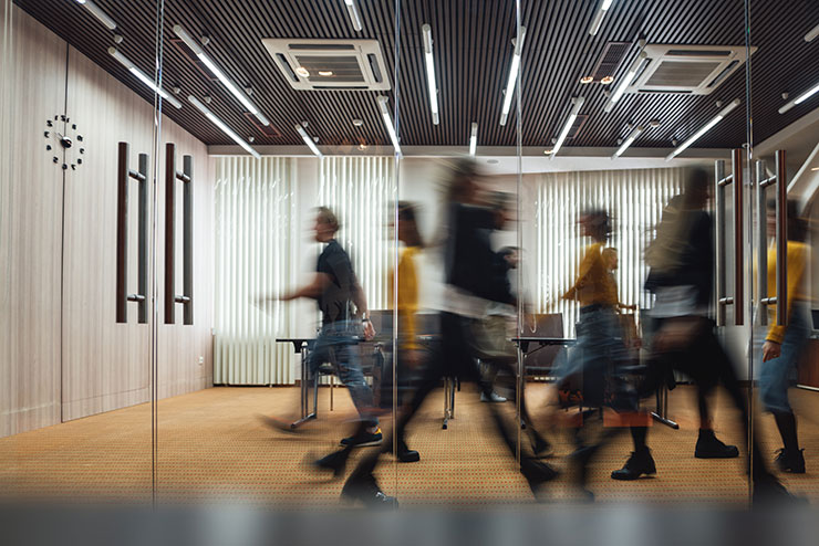 Motion blur image of people walking in office