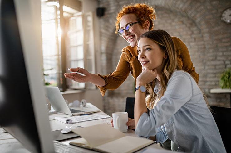 Deux travailleurs sourient devant un écran d'ordinateur