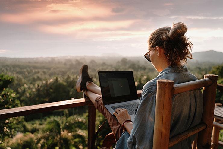 Personne travaillant à son ordinateur portable à l'extérieur, avec vue sur la forêt