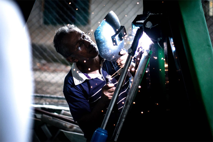 Older blue-collar worker wearing face shield sodering
