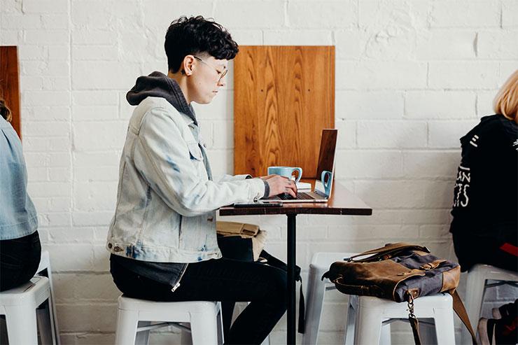 Une personne consulte un ordinateur portable sur la terrasse d'un café : les changements au recrutement et à l'embauche découlant de la COVID-19