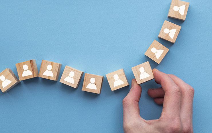 Tendances d'embauche 2021 : main qui choisit un cube de bois avec l'image d'une personne