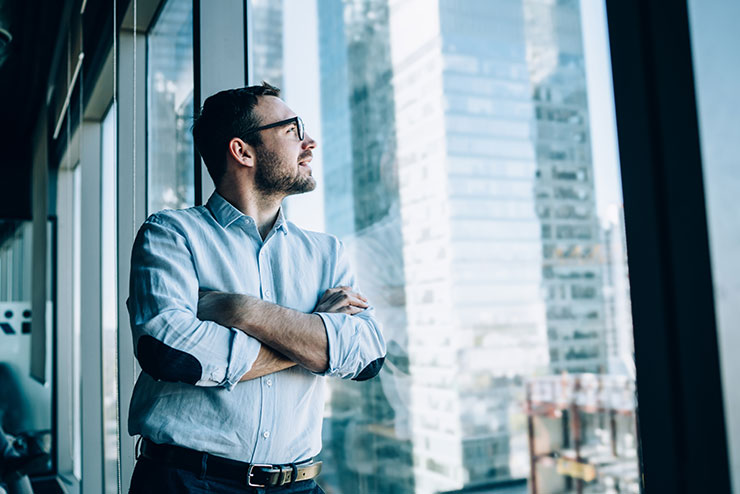 Person staring out office building window