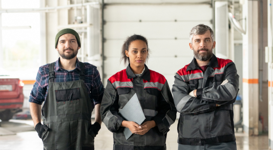 Three auto workers pose in the repair shop