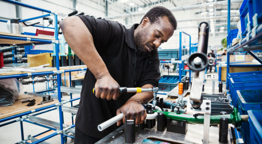 Male skilled factory worker man holding a tool