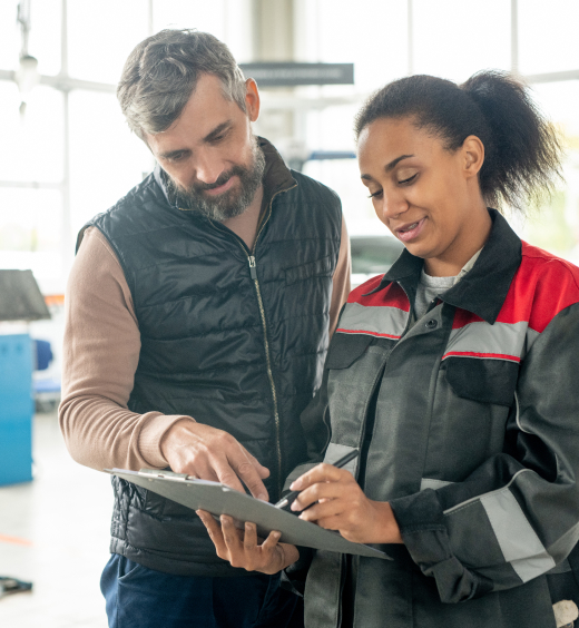 Young female automotive worker explaining a bill to her customer