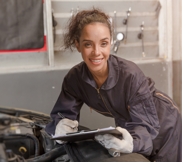 Young female mechanic works under the hood