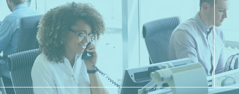 Young female smiling while answering the phone in an open-office.