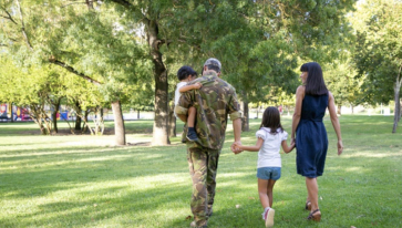 Service member in combat uniform holding a child and holding hands with another child who is holding the hand of their mother, walking through a grassfield with tree cover.