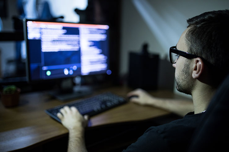 Worker with glasses sitting in front of computer.