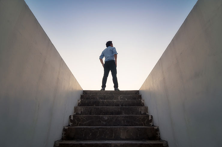 Person stands at top of underground staircase, looking at sky