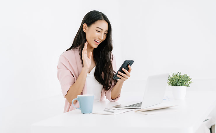 Woman sitting at desk waving hello to mobile phone