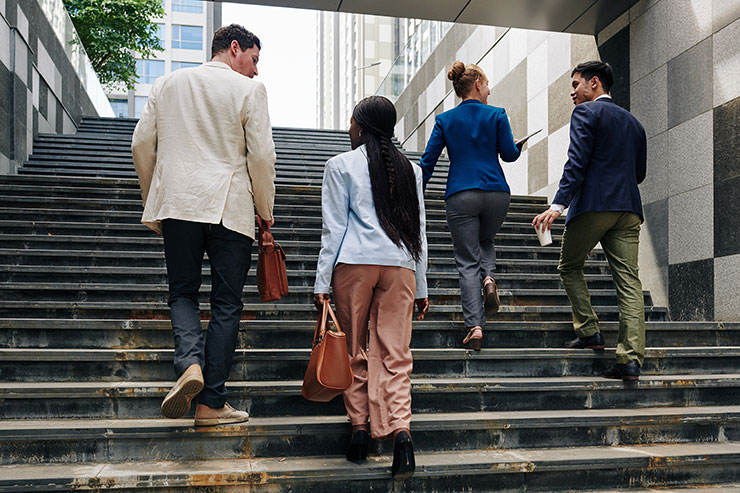 Four business people climbing stairs outdoors.