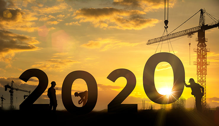 Silhouette of engineer and construction team setting up large 2020 sign