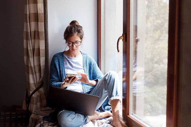 Social distancing in Covid-19 outbreak: Young woman working from home office.