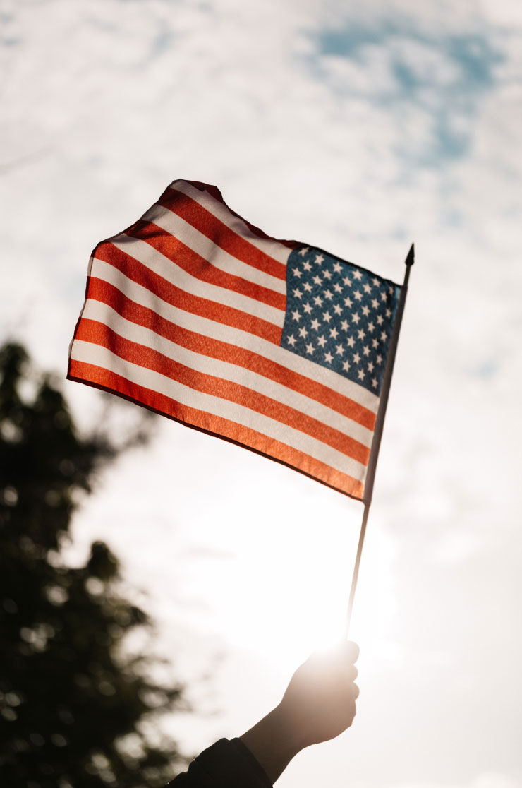Flag of the United States of America being held up by a sleeved hand, backlit by the warmth of the sun.