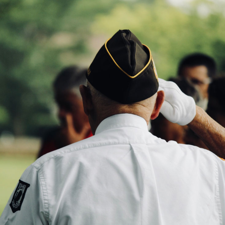 A view of an elder veteran of the U.S. military in his Dress Uniform soluting, actively soluting with a gloved hand.